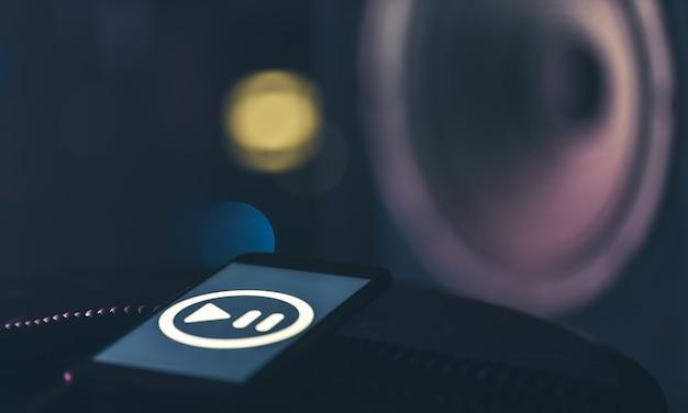Telefone com ícone de escuta de música na tela em fundo escuro, copie o espaço.