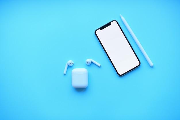 Telefone com lápis e cápsulas de ar em fundo azul