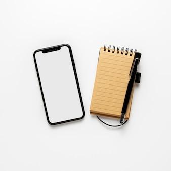 Telefone com vista superior perto do bloco de notas