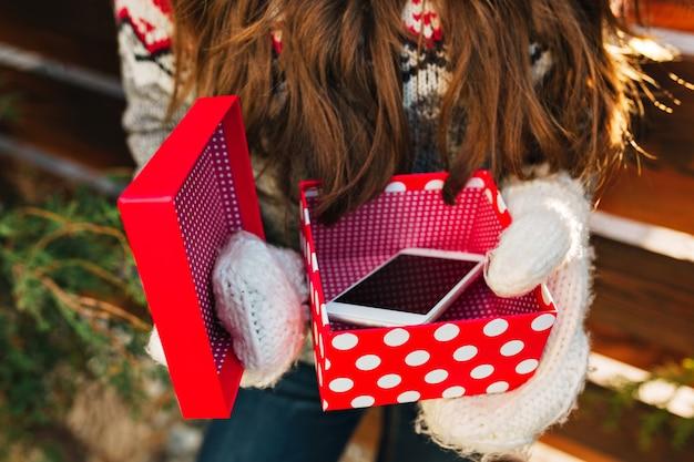 Telefone como presente de natal em uma caixa vermelha, segurando nas luvas da menina bonita.