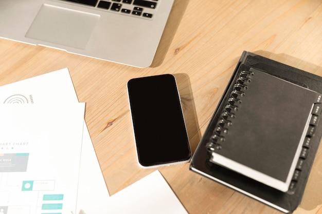 Telefone de alto ângulo e agenda na mesa