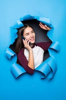 Telefone de conversa de mulher bonita jovem enquanto olha pelo buraco azul na parede de papel.