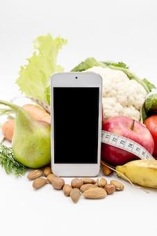 Telefone de exibição em branco com vegetais em pano de fundo branco