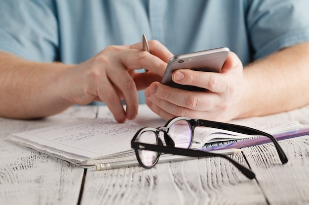 Telefone de mão de homem e calculadora na mesa de escritório