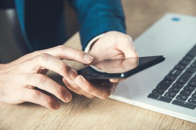 Telefone de mão de homem na mesa do escritório