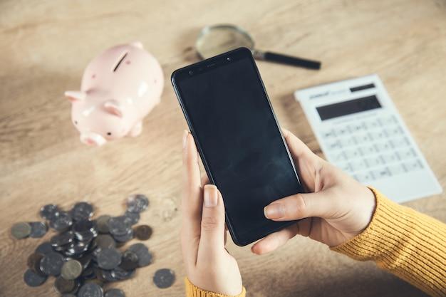 Telefone de mão de mulher com moedas e calculadora na mesa