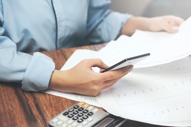 Telefone de mão de mulher de negócios e documentos no escritório