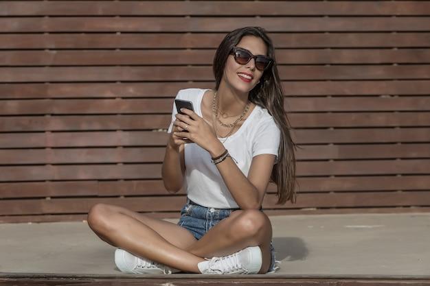 Telefone de navegação feminino sorridente enquanto relaxa no parque