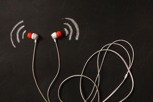 Telefone de orelha com ondas sonoras desenhadas no quadro-negro