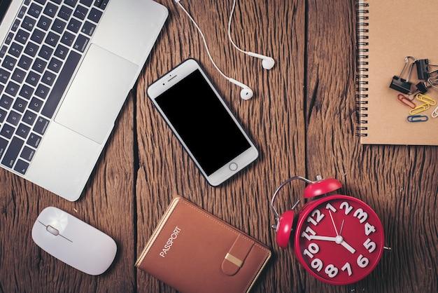 Telefone de vista superior e espaço de trabalho em fundo de madeira