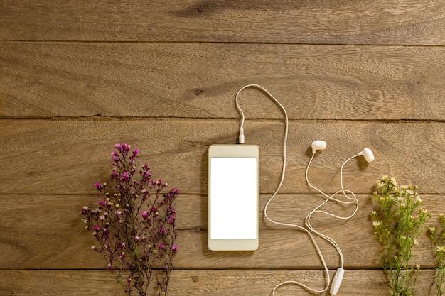 Telefone de vista superior e fundo de madeira de fone de ouvido