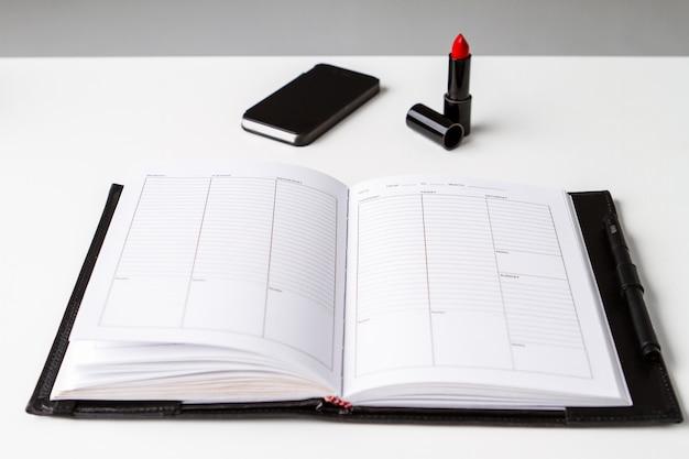 Telefone e caderno vermelhos do batom sobre a superfície branca acima.