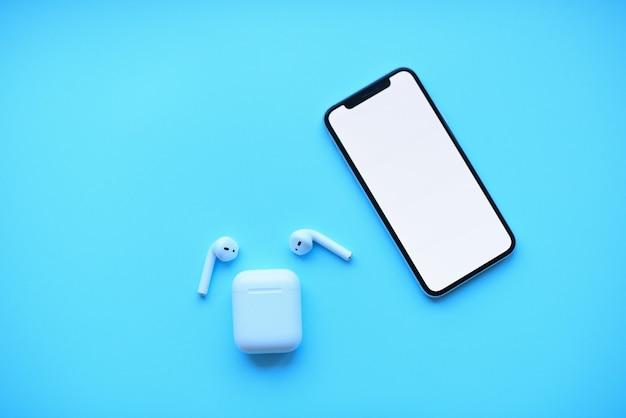 Telefone e pods de ar em fundo azul