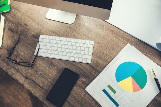 Telefone em papel milimetrado com teclado na mesa de trabalho