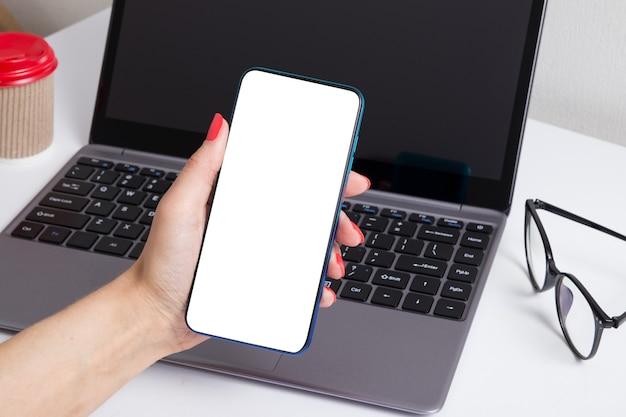 Telefone em uma mão feminina em um laptop e óculos