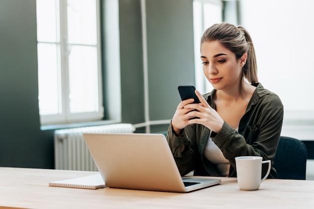 Telefone esperto da posse fêmea atrativa do freelancer ao sentar-se na frente do portátil.