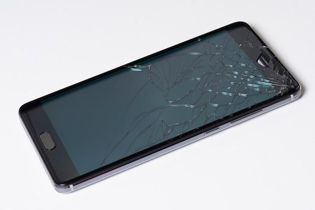 Telefone esperto móvel moderno da tela de toque com a tela quebrada no fundo branco