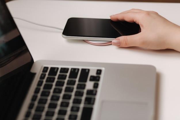 Telefone feminino mão tup no carregamento sem fio. local de trabalho próximo ao laptop. vista do topo.