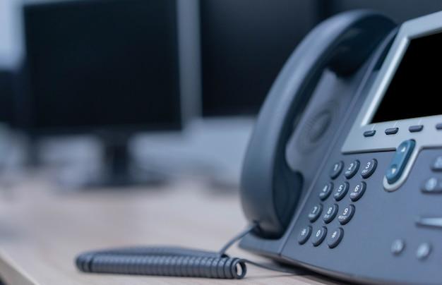Telefone fixo no escritório para tecnologia de telecomunicações e conceito de negócios