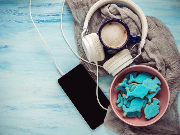 Telefone, fones de ouvido, uma xícara de cappuccino perfumado