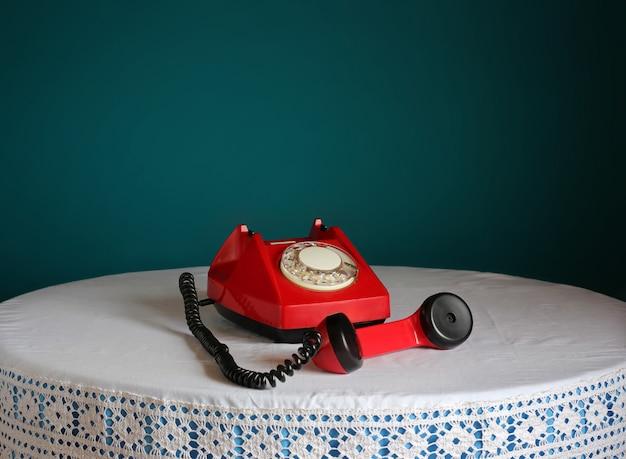 Telefone giratório retro vermelho em uma mesa redonda.