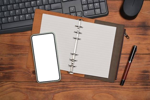 Telefone inteligente, caderno e caneta na mesa de madeira.
