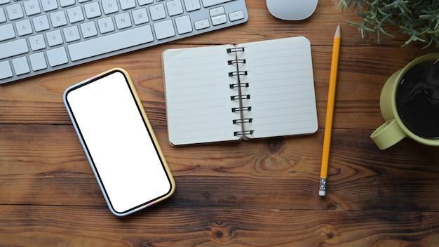 Telefone inteligente, caderno e xícara de café na mesa de madeira.