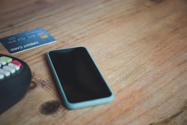 Telefone inteligente, cartão de crédito e máquina de pagamento na mesa com espaço de cópia
