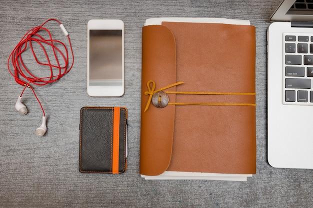Telefone inteligente, carteira, fones de ouvido e um notebook de couro em uma mesa preta. vista do topo