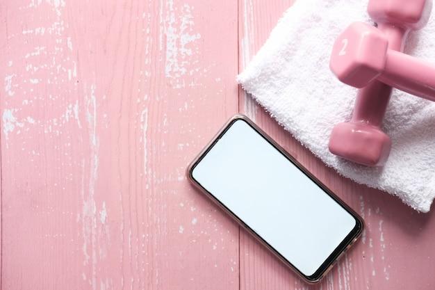 Telefone inteligente com equipamento desportivo no espaço rosa.