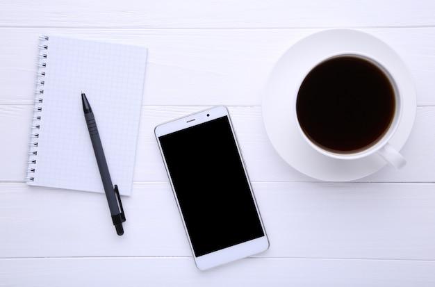 Telefone inteligente com notebook e xícara de café sobre fundo branco de madeira