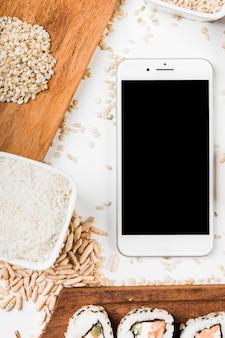 Telefone inteligente com sushi; arroz cru e folhado