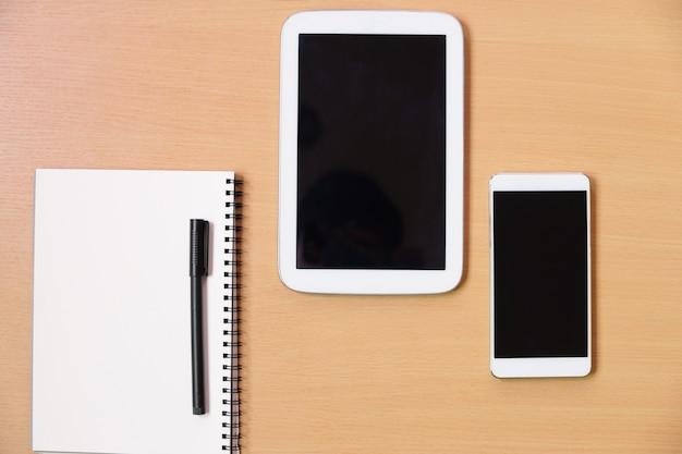 Telefone inteligente com taplet, papel de caderno, caneta preta sobre fundo de mesa de escritório de madeira