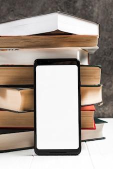 Telefone inteligente com tela branca na frente de livros empilhados vintage