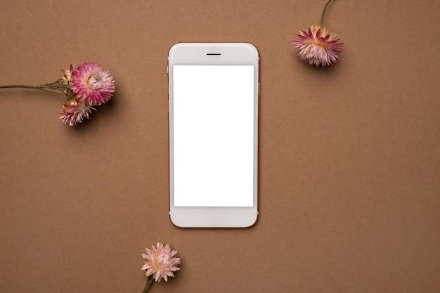 Telefone inteligente com tela em branco em uma moldura de flores secas na superfície marrom