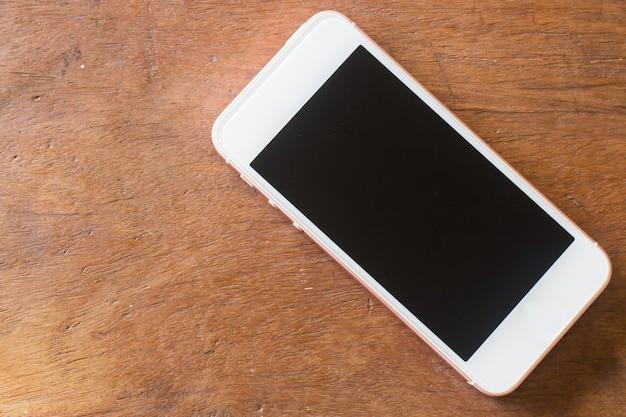 Telefone inteligente com tela em branco na mesa de madeira
