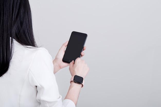 Telefone inteligente de mão de mulher e relógio inteligente