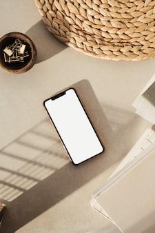 Telefone inteligente de tela em branco, cadernos, clipes em uma tigela de madeira, suporte de palha no fundo bege de concreto. área de trabalho da mesa do escritório doméstico