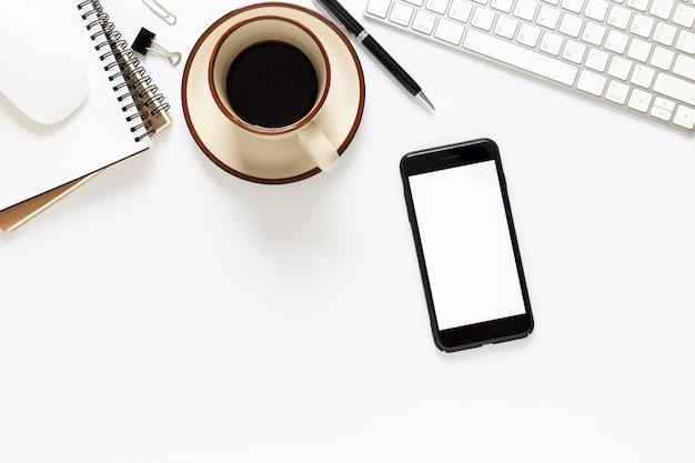 Telefone inteligente de tela em branco e computador na vista superior de fundo branco.