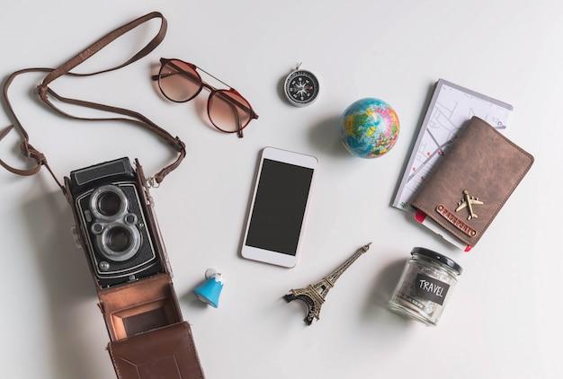 Telefone inteligente de tela vazia com acessórios de viagem e itens em fundo branco, com espaço de cópia
