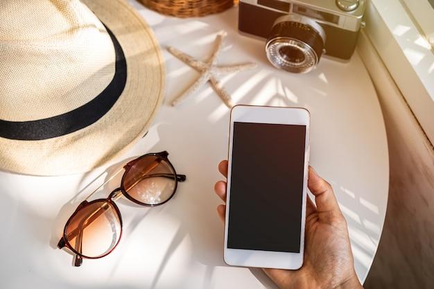 Telefone inteligente de tela vazia com acessórios de viagem em cima da mesa, conceito de férias de verão