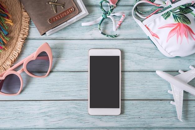 Telefone inteligente de tela vazia com acessórios para viagens de verão e itens em fundo de madeira