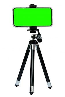 Telefone inteligente de tela verde no tripé isolado no branco com traçado de recorte