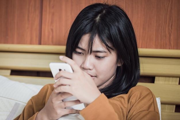 Telefone inteligente e conceito de ensino: asiáticos estudantes ou adolescentes usando smartphone conversando