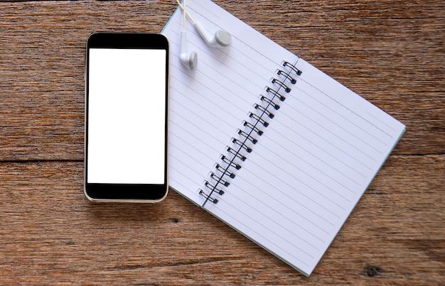 Telefone inteligente e fone de ouvido com notebook no piso de madeira