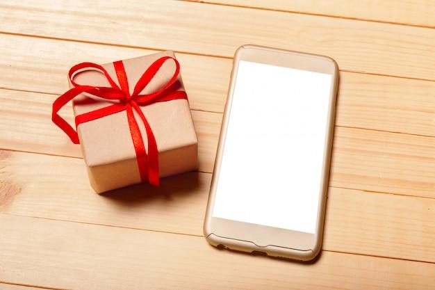Telefone inteligente e presente em fundo de madeira