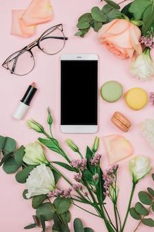 Telefone inteligente em branco; óculos; batom; rosa; limonium e eustoma flores sobre fundo rosa