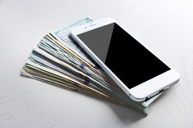 Telefone inteligente em uma pilha de notas de dólar na mesa branca.