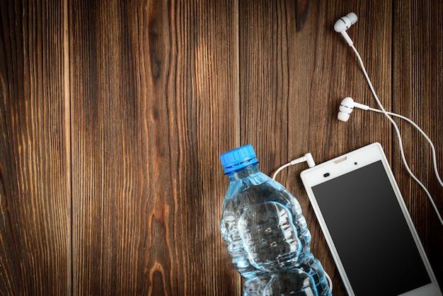 Telefone inteligente, fones de ouvido e garrafa de água na mesa de madeira.