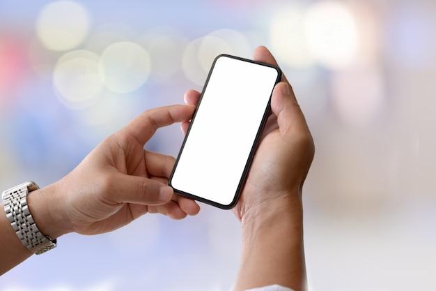 Telefone inteligente móvel de tela em branco no masculino mão sobre fundo de luz bokeh
